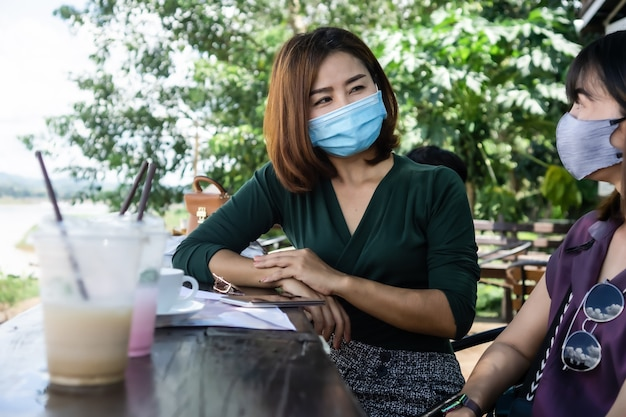 Two asian female friend wearing protective mask  talking outdoors