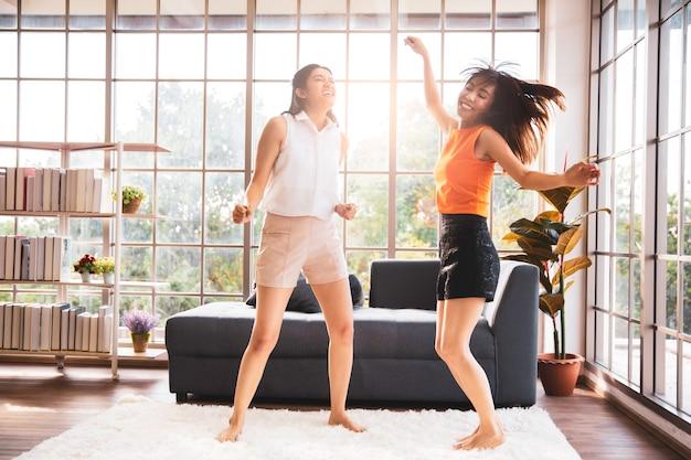 Две азиатские подруги танцуют в гостиной