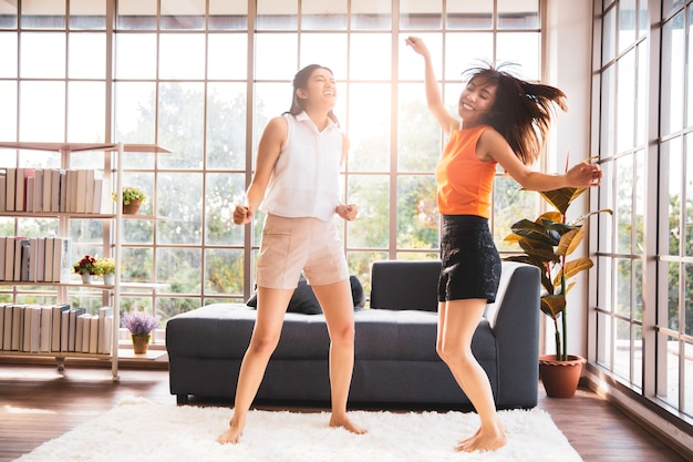 Two asian female friends dancing in living room