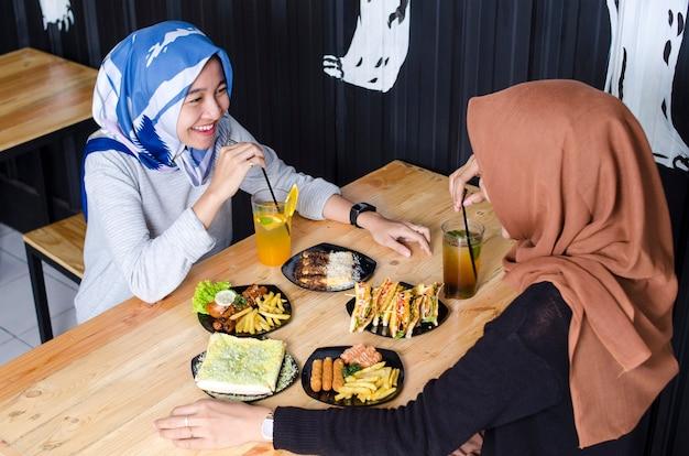 두 명의 아시아 여성 히잡이 음식을 먹고 군중 레스토랑에서 친구들과 웃고 있다
