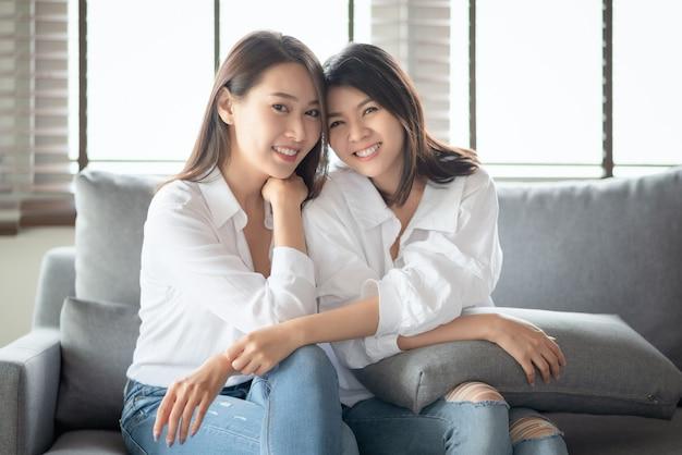 두 아시아 여성이 집에서 거실에서 매력적인 미소로 인물 사진을 찍습니다.