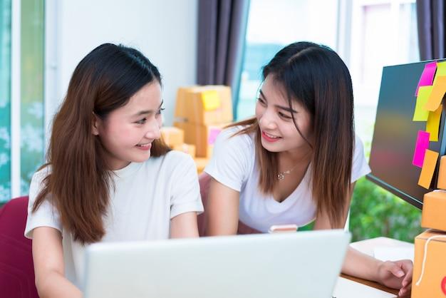 ラップトップを使うときに一緒に見える2人のアジアの友情女性