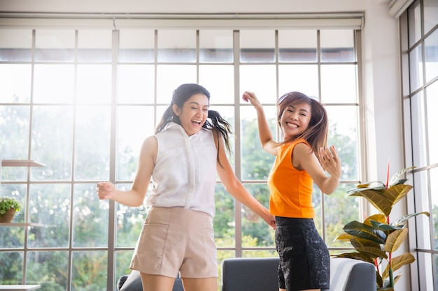 Two asian girl friends dancing in living room at home
