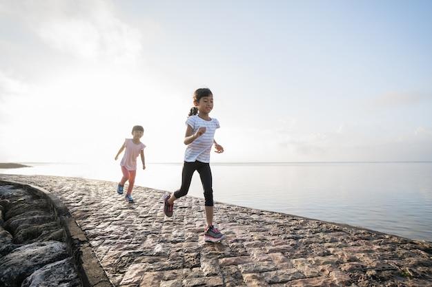 2人のアジアの女の子がビーチでジョギングしています