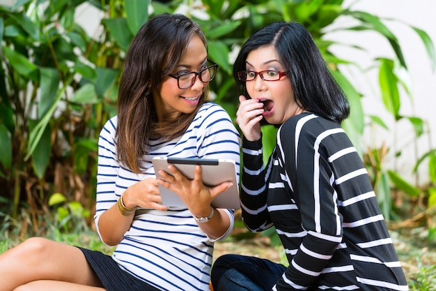 Two asian girlfriends with tablet computer