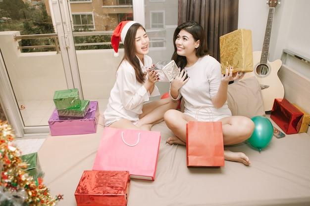 Две девушки из азии счастливы на рождество.