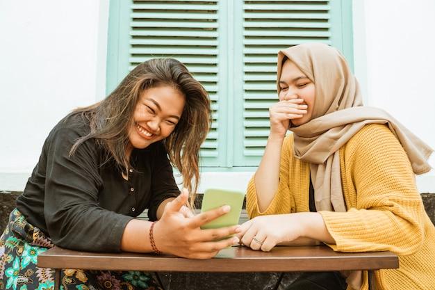 チャットと携帯電話を保持している2人のアジアの女の子