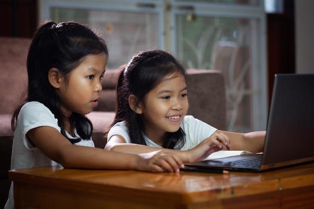 オンラインレッスンをしている2人のアジアの女の子