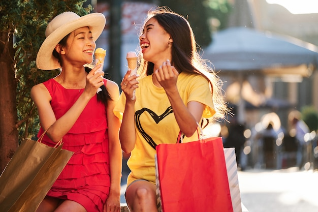 Two asian girls eating ice cream on at sunset in an urban bench