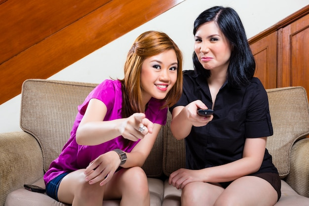 Two asian girls at home watching tv