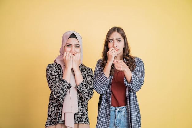 겁 먹은 표정을 보고 카메라를 가리키는 두 아시아 소녀