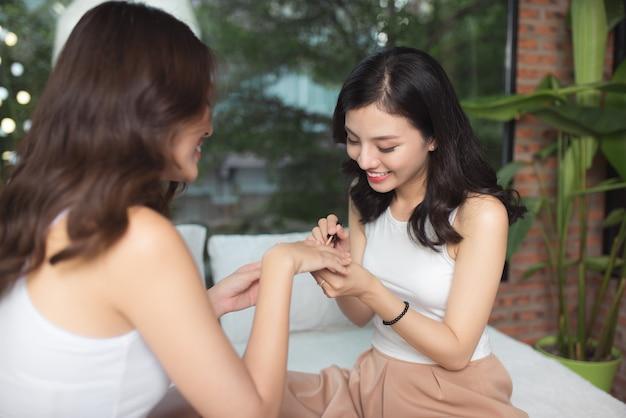 リビング ルームのベッドで足の爪と指の爪を描く 2 人のアジアの女の子