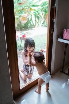 窓ガラスを通してお互いに微笑んでいる2人のアジアの女の子
