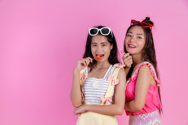 Two asian girls who are friends are happy and have a pink .