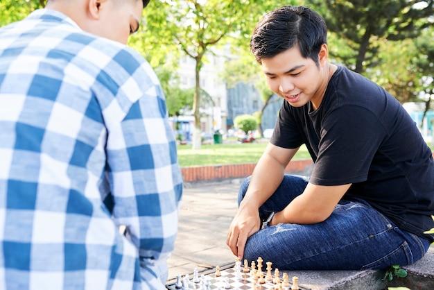 Два азиатских парня сидят на скамейке на улице и вместе играют в шахматы
