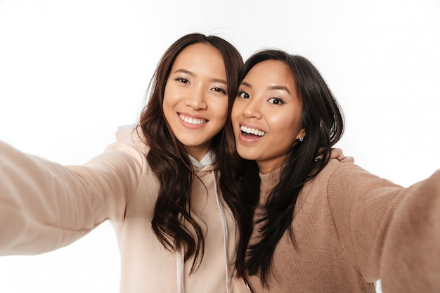 Two asian happy positive ladies sisters