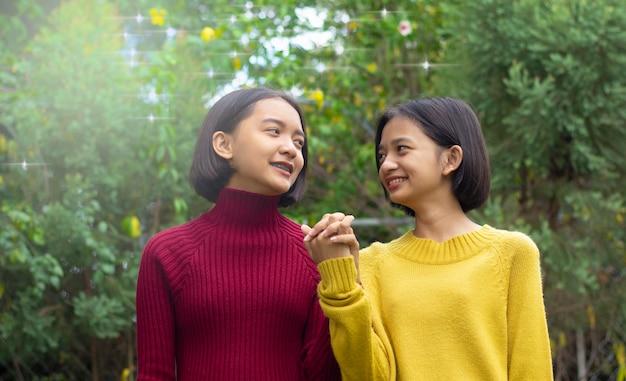 Две азиатские счастливые молодые девушки на природе