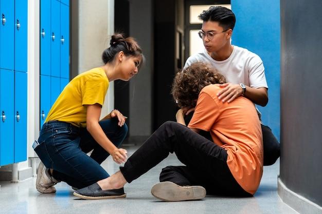 Двое азиатских старшеклассников утешают грустного одноклассника, ставшего жертвой издевательств в коридоре.