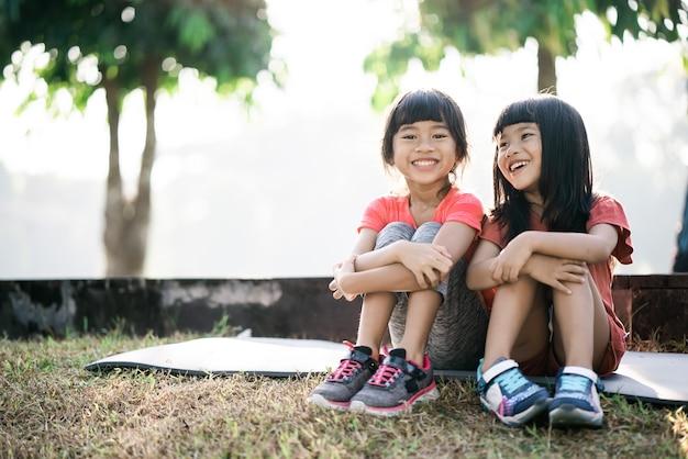 2人のアジアの子供が朝公園で休憩している
