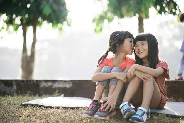 2人のアジアの子供たちが朝公園で休憩している