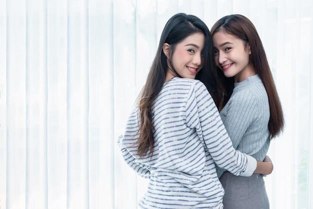 寝室で一緒に探している2人のアジアのレズビアンの女性