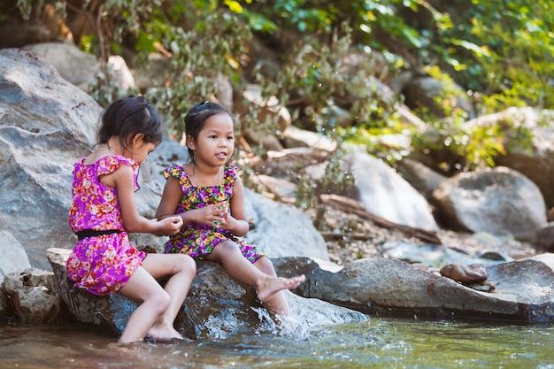 岩の上に座って川沿いの水を再生する2人のアジアの小さな子供の女の子