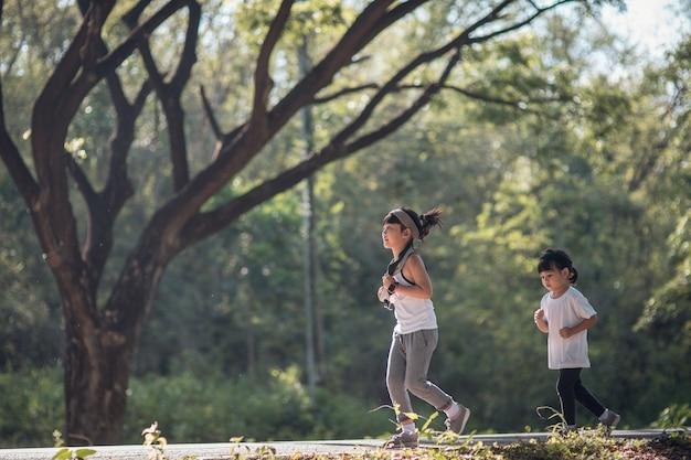 두 명의 아시아 소녀들이 빈티지한 색조로 공원에서 함께 즐겁게 뛰고 있습니다.
