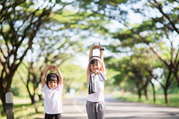 楽しんで、ヴィンテージの色調で公園で一緒に走っている2人のアジアの少女