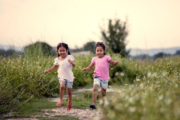 Two asian little girls having fun and running together in the park in vintage color tone