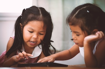 Two asian little girls having fun watching videos in a tablet.