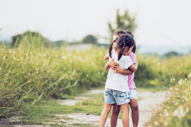 Two asian little girls hugging each other with love in vintage color tone