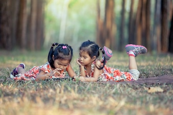 Two asian little girls lying on the grass and using tablet in the park in vintage color tone