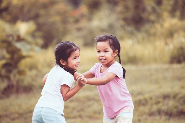 Two asian little girls playing together in the park in vintage color tone