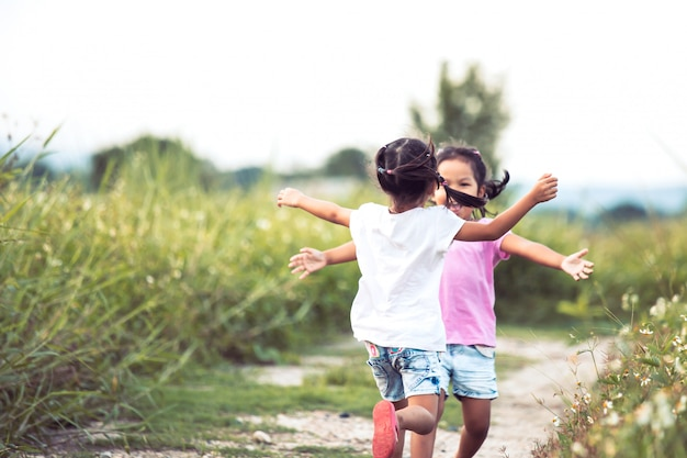 Two asian little girls running to give a hug each other in vintage color tone