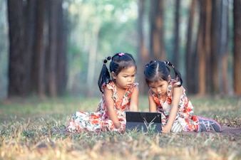 Two asian little girls sitting on the grass and using tablet in the park in vintage color tone