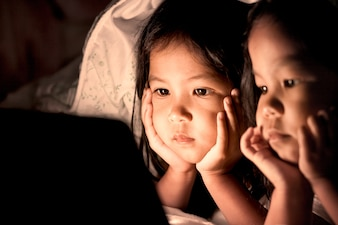 Two asian little girls using digital tablet under blanket at night in vintage color tone