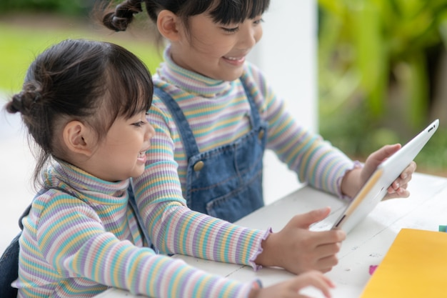自宅でデジタルタブレットで遊んでいる2人のアジアの妹