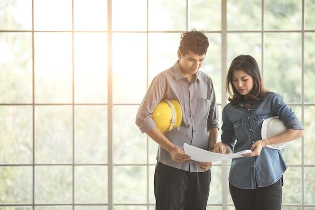 Два азиатских инженера мужского и женского пола держат белый и желтый защитный шлем стоя и разговаривают вместе. стеклянная рамка в фоновом режиме