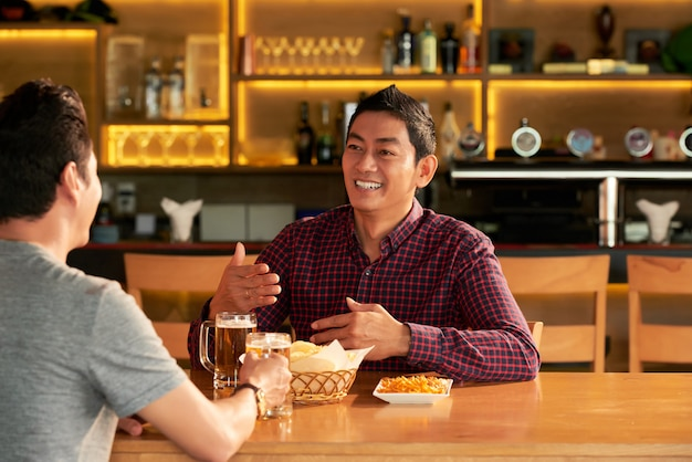 Two asian male friends sitting at table in bar with mugs of beer and snacks and chatting