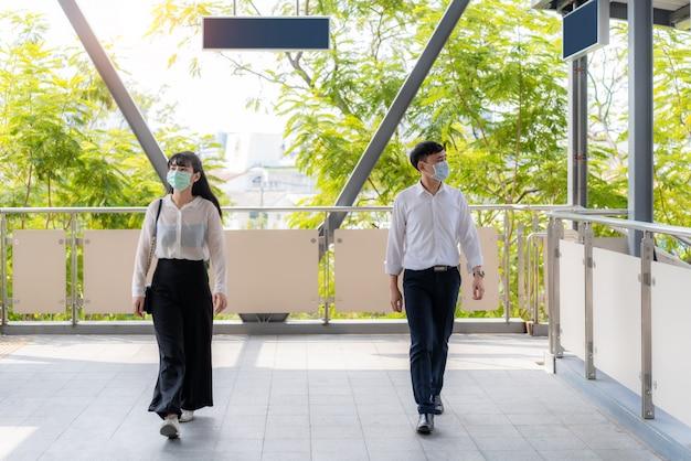 2 명의 아시아 남자와 여자는 감염 위험과 질병 예방을 위해 사회적 거리를두고 보도 나 스카이 워크를 걷는 사람 사이에 2 미터 또는 6 피트의 거리를 유지합니다 covid-19.