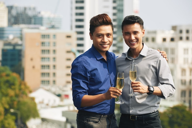 Two asian men holding champagne flutes, hugging and posing together at urban rooftop party