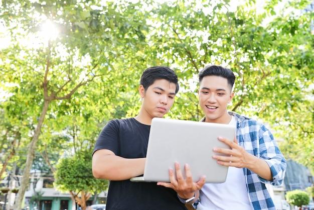 ラップトップを持って、屋外の街で一緒に使用している2人のアジア人男性