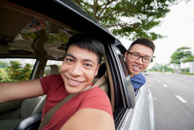 Two asian men riding in car on road and looking out, and driver taking selfie