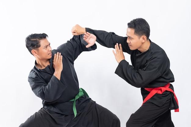 プンチャックシラットのユニフォームを着た2人のアジア人男性が、パンチとタンキサンアタスの動きで戦う