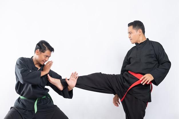 プンチャックシラットのユニフォームを着た2人のアジア人男性が、テンダンガンルルスとタンキサンと戦う