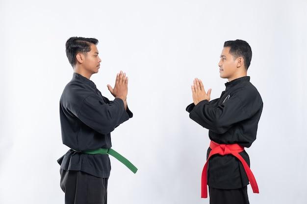 プンチャックシラットのユニフォームを着た2人のアジア人男性がお互いを尊重して向かい合って立っています
