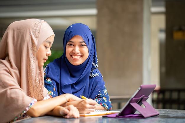 Два азиатских мусалима работают и обсуждают с планшетом в офисе.