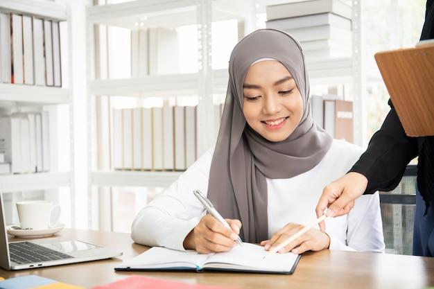 2つのアジアのイスラム教徒のビジネスウーマンが話して、オフィスで一緒に働いています。
