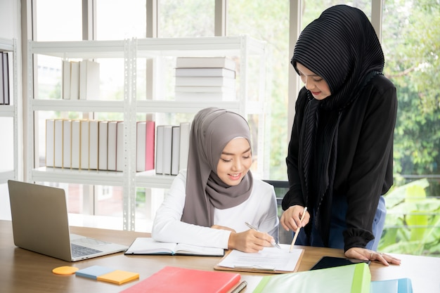 Two asian muslim businesswomen talking and working together in the office