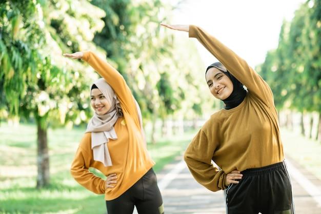 スカーフを着た2人のアジアのイスラム教徒の少女が、公園の部屋の外で運動するために手を上げて筋肉を伸ばします。